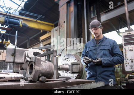 Engineer at lathe in engineering factory - Stock Photo