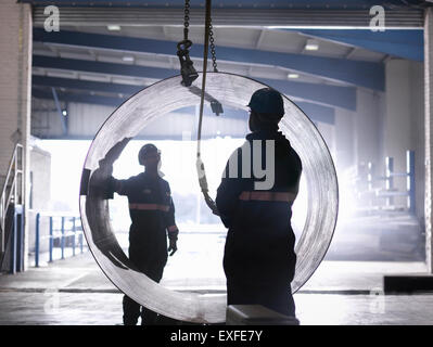 Engineers using crane to lift large steel tube in engineering factory - Stock Photo