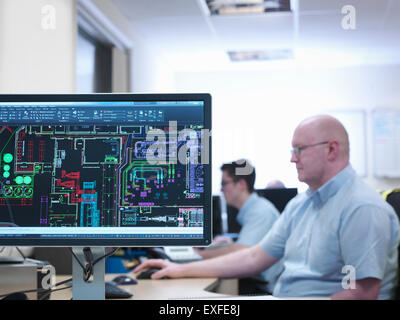 Engineers looking at CAD designs in office of engineering factory - Stock Photo