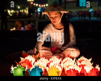 Vietnamese woman selling candle offerings during Chinese New Year celebrations in Hoi An, Vietnam. - Stock Photo