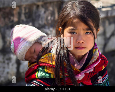 Unidentified Hmong girl carrying baby and wearing traditional attire in Sapa town, Lao Cai, Vietnam. - Stock Photo