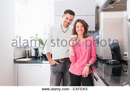 Portrait of young couple in kitchen with glass of milk - Stock Photo