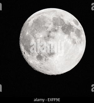 Full moon minus a few hours with a ragged crater lined edge and star speckled space behind - photographed in the - Stock Photo