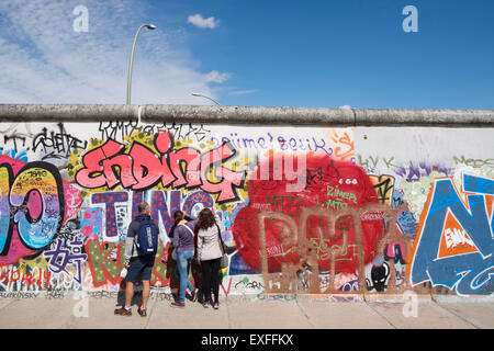 Graffiti on original section of Berlin Wall at the East Side Gallery in Friedrichshain Berlin Germany - Stock Photo
