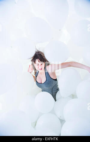 Globophobia: a young woman girl alone in a cloud of hundreds of white balloons fighting struggling against her irrational - Stock Photo