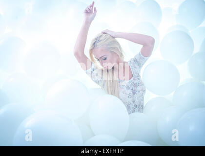Dreamland: a young blonde haired woman girl alone in a cloud of hundreds of white balloons, laying back, as if asleep - Stock Photo