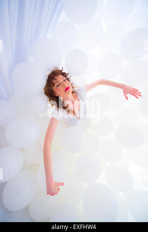 Dreamland: a young woman girl alone in a cloud of hundreds of white balloons, laying back, as if asleep - Stock Photo