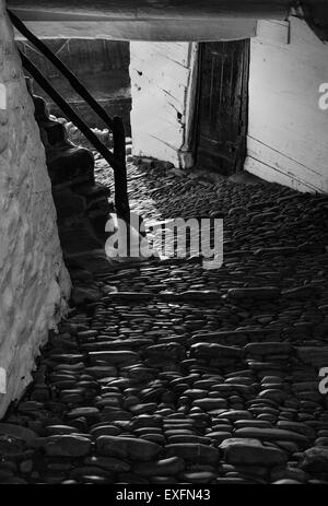 Cobbled road passing through a house and down to the harbour in the pretty Devon village of Clovelly UK - Stock Photo