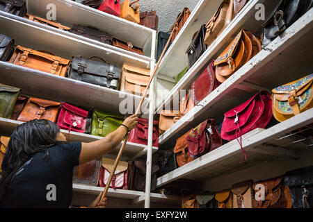 Woman reaching to get leather handbag from top shelf in a stall at a market  in 34d48033d8f7f