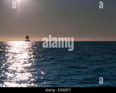 Maori sailing waka of Tauranga coast, on horizon soon after sunrise. - Stock Photo