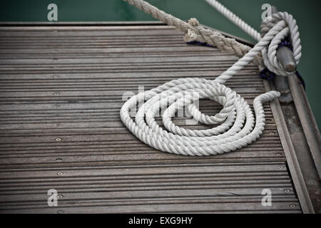 A mooring rope with a knotted end tied around a cleat on a wooden pier - Stock Photo