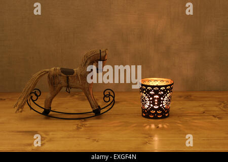 Christmas decoration - wooden toy rocking-horse and candle in candlestick on wooden table against concrete wall - Stock Photo