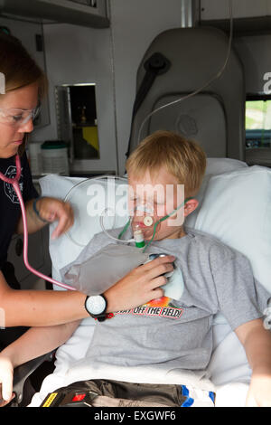 Female paramedic assisting young male patient in back of ambulance. - Stock Photo