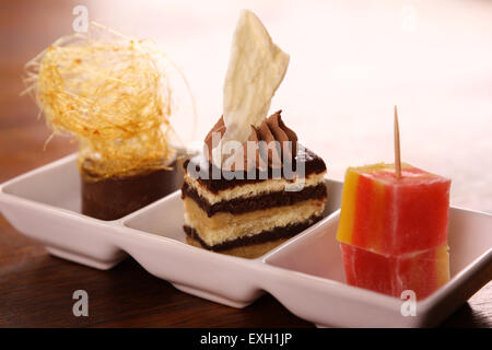 Three beautiful delicious gourmet desserts on a white plate. Chocolate layered cake, fudge, mousse and turkish delights. - Stock Photo