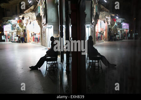 Cairo, Egypt. 26th June, 2015. Egyptian men take rest on a main commercial street lined by empty shops in downtown - Stock Photo
