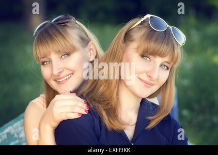 Portrait of twins sisters at the park. Two young beautiful girls looking straight. Warm color toned image - Stock Photo