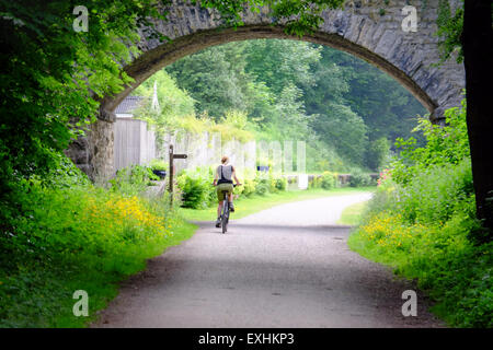 Female cyclist at Hassop on the Monsal Trail cycling route between Buxton and Bakewell in the Peak District, UK - Stock Photo