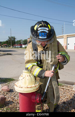 Female firefighter in rural volunteer fire department working with equipment. - Stock Photo