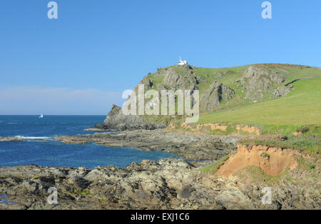 View Across Rocks to East Prawle Lighthouse on the South West Coastal Path, near Salcombe, on the South Devon Coast, - Stock Photo