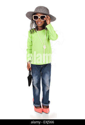 Adorable small african child with braids wearing a bright green shirt and blue jeans. The girl is playing dress - Stock Photo