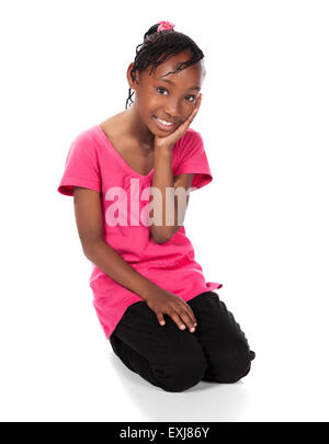 Adorable small african child with braids wearing a bright green shirt and black skinny jeans. The girl is sitting - Stock Photo