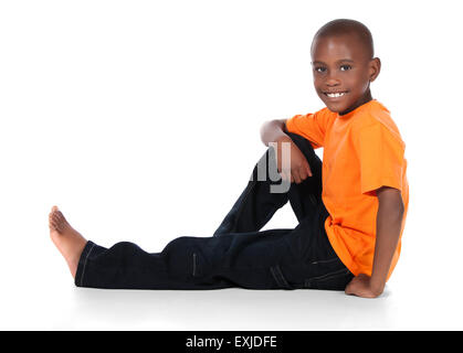 Cute african boy wearing a bright orange t-shirt and dark denim jeans. The boy is sitting and smiling at the camera. - Stock Photo
