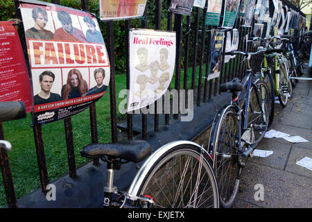 Advertising posters and bikes against railings in Cambridge - Stock Photo