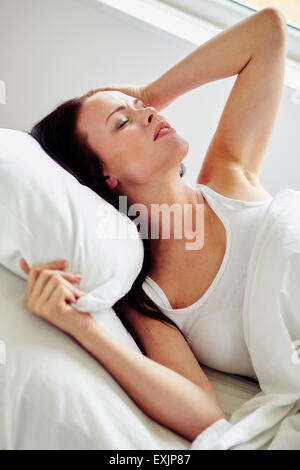 Girl laid in bed not able to sleep - Stock Photo