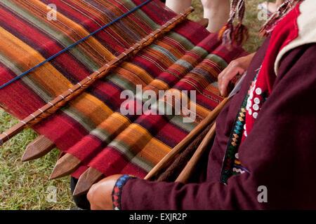 Peruvian man from Chinchero weaving traditional fabric using back strap loom - Stock Photo