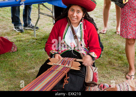 Peruvian woman from Chinchero weaving traditional fabric using a back strap loom - Stock Photo