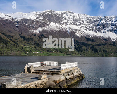 bench on pier at Dalsören campsite, viewpoint, snow covered mountains at the fjord, Lustrafjord, inner branch of - Stock Photo