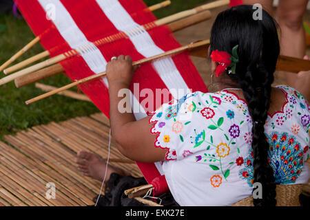 Peruvian woman from Chinchero weaving traditional fabric using back strap loom - Stock Photo
