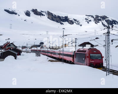 Train passing Finse railway station, area covered with snow in late spring, highest railway station on railway Oslo - Stock Photo