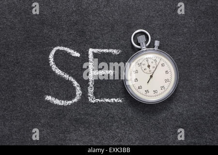 SEO abbreviation concept handwritten on chalkboard with vintage precise stopwatch used instead of O - Stock Photo