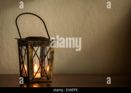 Lantern with a burning candle on wooden surface with copy space. - Stock Photo