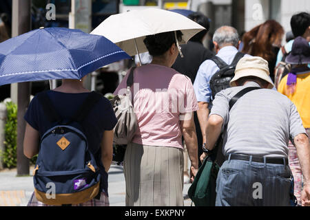 Pedestrians hold parasols to get some shade in the hot weather in Shinjuku district on July 15, 2015, Tokyo, Japan. - Stock Photo
