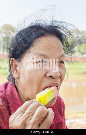 Closeup of Asian Thai old woman eating ice cream - Stock Photo