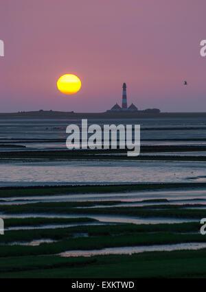 Westerhever Lighthouse at sunset behind Tümlau Bay, Tümlauer-Koog, Westerheversand, Schleswig-Holstein, Germany - Stock Photo