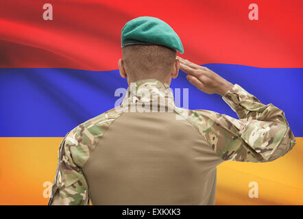Dark-skinned soldier in hat facing national flag series - Armenia - Stock Photo