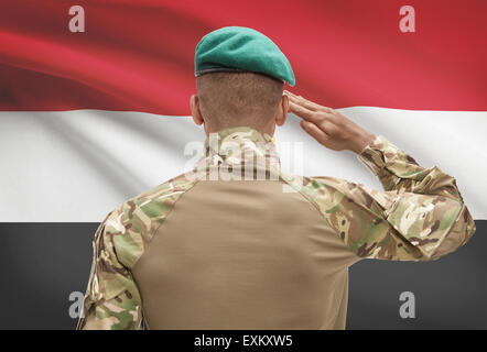 Dark-skinned soldier in hat facing national flag series - Egypt - Stock Photo