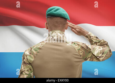 Dark-skinned soldier in hat facing national flag series - Luxembourg - Stock Photo