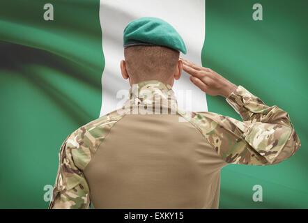 Dark-skinned soldier in hat facing national flag series - Nigeria - Stock Photo