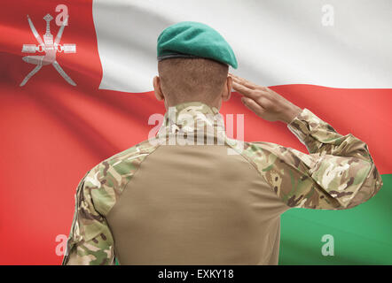 Dark-skinned soldier in hat facing national flag series - Oman - Stock Photo