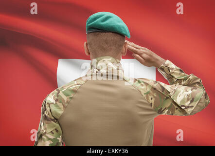 Dark-skinned soldier in hat facing national flag series - Switzerland - Stock Photo