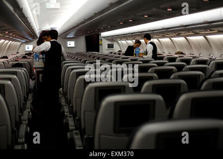 crew serving refreshments to passengers in an almost deserted economy cabin on a qatar airlines flight from jakarta to doha