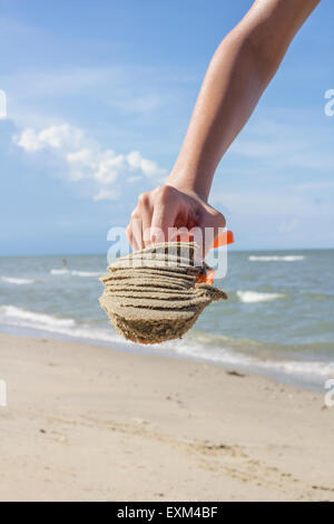 Close up hand of Asian Thai boy holding plastic shovel with sand on tropical beach at the day time - Stock Photo