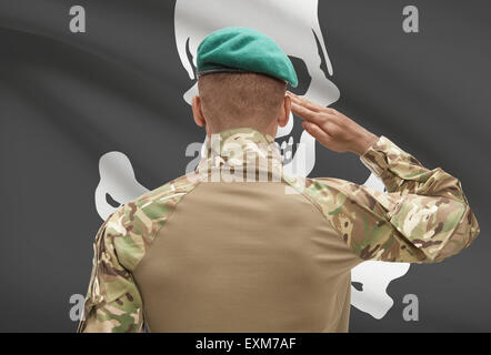 Dark-skinned soldier in hat facing flag series - Jolly Roger - Stock Photo