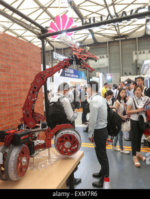 Shanghai, China. 15th July, 2015. Spectators watch a robot at Mobile World Congress (MWC) with the theme of Mobile Infinity in Shanghai, east China, July 15, 2015. © Ding Ting/Xinhua/Alamy Live News Stock Photo