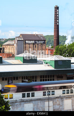 The old chimney of Brains Brewery and Cardiff train station in the foreground. - Stock Photo