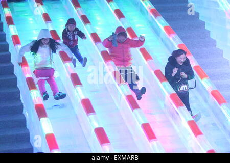Yantai, China's Shandong Province. 15th July, 2015. People play on icy slides at an ice sculpture exhibition in - Stock Photo